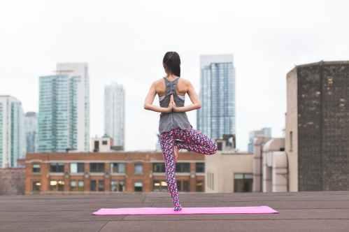 woman standing on pink yoga mat meditating